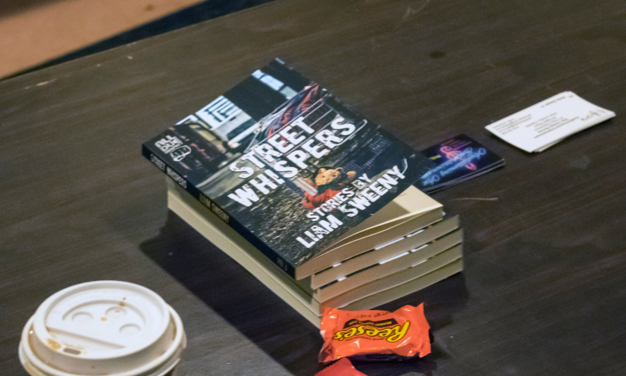 Copies of Street Whispers book on table.